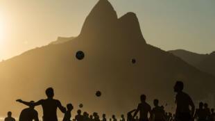 Des gens jouent au foot sur la plage d'Ipanema, à Rio.