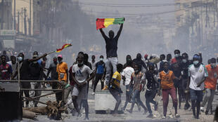 A demonstrator holds up a Senegalese flag during protests against the arrest of opposition leader and former presidential candidate Ousmane Sonko in Dakar, Senegal, on March 5, 2021.
