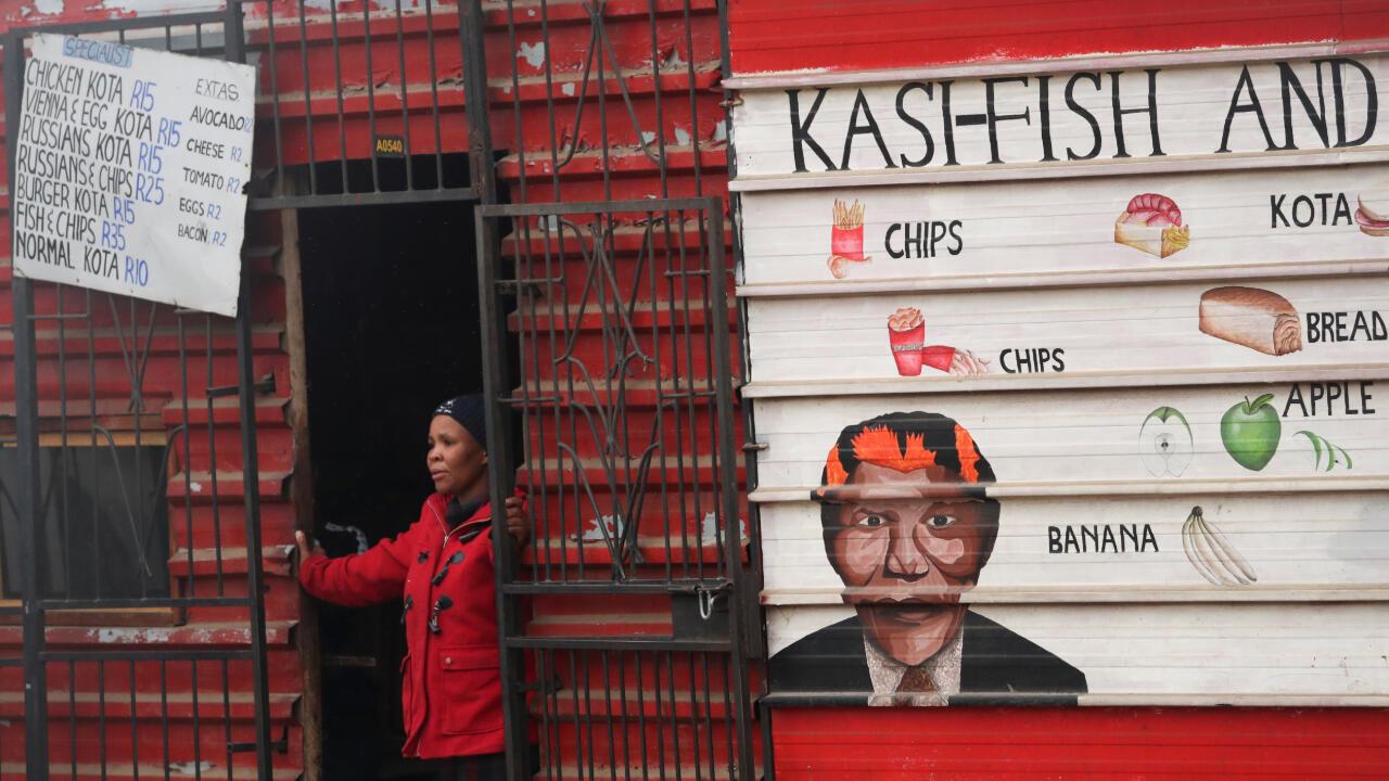 La dueña de una tienda observa cómo la policía dispersa a los manifestantes durante una protesta contra las desigualdades raciales y económicas en el municipio de Kayamandi cerca de Stellenbosch, Sudáfrica, 12 de agosto de 2020.