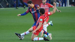 La star du Barça Lionel Messi taclé par le défenseur de Grenade German Sanchez, le 29 avril 2021 à Barcelone