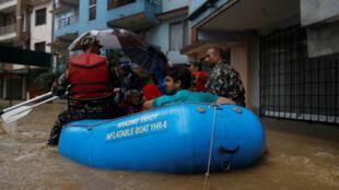 Des habitants de la capitale népalaise, Katmandou, flottent dans la ville à l'aide d'un bateau, en pleine mousson, le 12 juillet 2019.