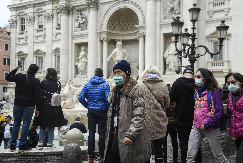 Los turistas asiáticos que usan máscaras respiratorias visitan la Fontana di Trevi en el centro de Roma, Italia, el 31 de enero de 2020.