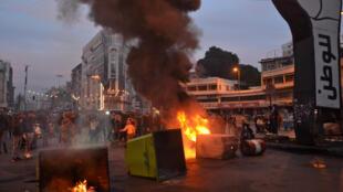Des bennes à ordures incendiées par des manifestants sur la place al-Nour, à Tripoli, au Liban, le 26 janvier 2021.