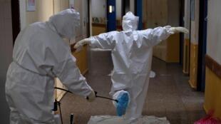Un operario desinfecta la indumentaria protectora de un miembro del personal sanitario antes de que entre en la unidad de cuidados intensivos del hospital San Rafael, el 16 de mayo de 2020 en Santa Tecla, a 10 km de San Salvador