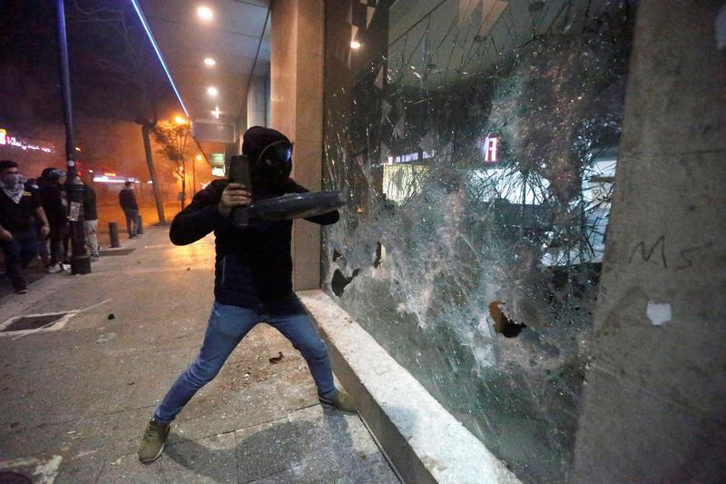 Protesters smash a bank window in Beirut, January 14, 2020.