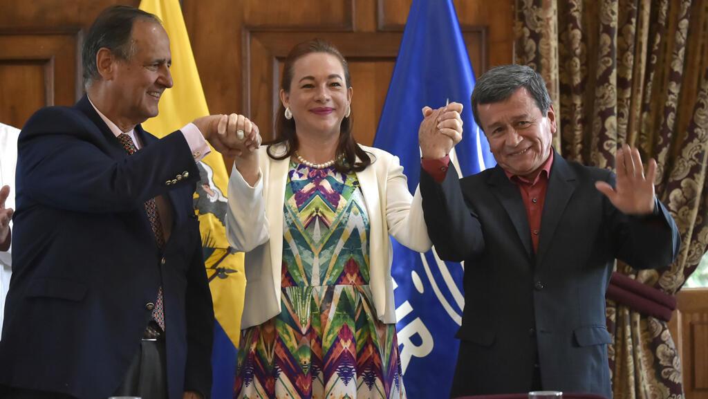 Ministra de asuntos exteriores de Ecuador, María Fernanda Espinoza, alza las manos del jefe de la delegación de paz del gobierno colombiano, Juan Camilo Restrepo y el jefe negociador de la guerrilla del ELN, Pablo Beltran. Quito, septiembre 4, 2017.