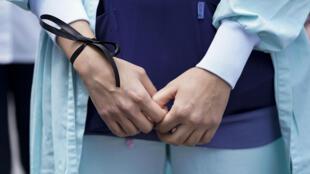 Una trabajadora sanitaria con un lazo negro en la muñeca reclama mejores condiciones laborales el 22 de junio de 2020 en un hospital de Bruselas