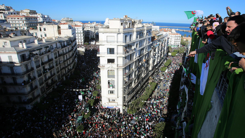 Manifestantes en lo alto de un edificio durante una protesta contra la decisión del presidente Abdelaziz Bouteflika de posponer las elecciones y extender su cuarto mandato en Argelia.