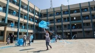 Palestinian girls fly kites in the courtyard of an UNRWA-run school in Gaza during a protest against US aid cuts that threatened their education until other donors stepped in