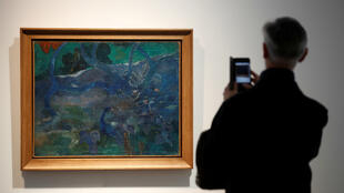"A man takes a picture of Paul Gaugin's ""Te Bourao II"" (The Purao Tree) painting (1897) at Artcurial's auction house in Paris, France, October 3, 2019."
