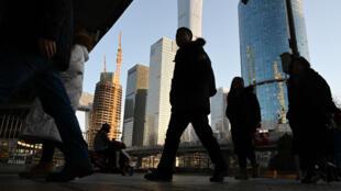 Ciudadanos chinos cruzan una calle en el distrito central de negocios de Beijing, China, el 21 de enero de 2019.
