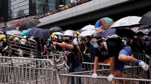 Un manifestante se monta a una barricada de metal durante una manifestación contra el polémico proyecto de ley de extradición en Hong Kong, China, 12 de junio de 2019.