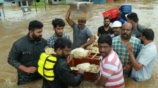 Un fermier indien et ses amis évacuent des poules menacées par les eaux, dans la région d'Ernakulam, le 17 août 2018.