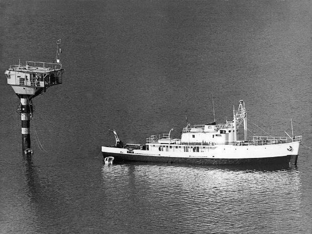 """La Calypso remorquant sa """"Soucoupe plongeante"""" dans la baie de Villefranche-sur-Mer, en Méditerranée, le 21 juin 1964."""