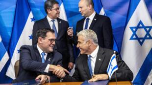 El canciller de Honduras, Lisandro Rosales (abajo a la izquierda) estrecha la mano de su homólogo israelí, Yair Lapid, mientras el presidente de Honduras, Juan Orlando Hernández (arriba a la izquierda), conversa con el primer ministro israelí, Naftali Bennett el 24 de junio de 2021 en Jerusalen