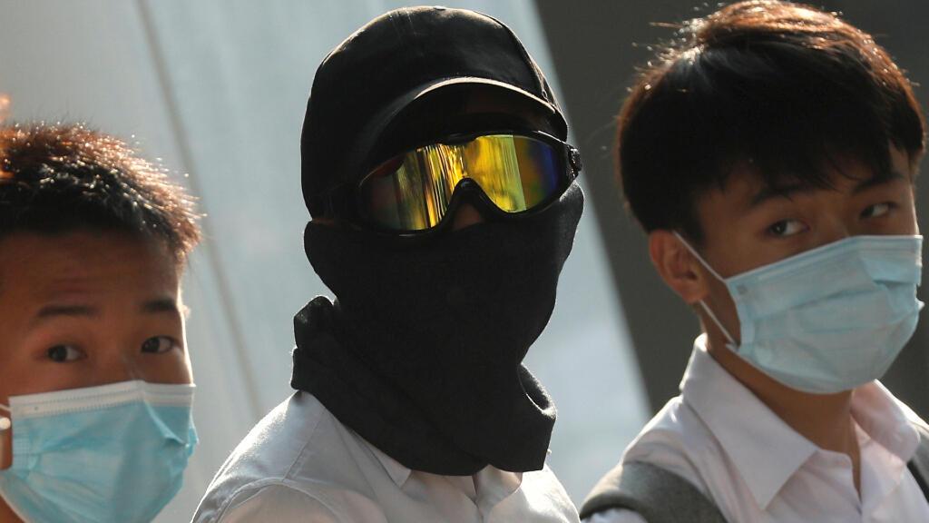 Estudiantes de secundaria con máscaras se unen a una cadena humana que protesta contra la brutalidad policial hacia los manifestantes, tras los enfrentamientos en el distrito de Wan Chai en Hong Kong este fin de semana.