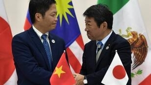 وزير الاقتصاد الياباني يصافح وزير التجارة الفيتنامي