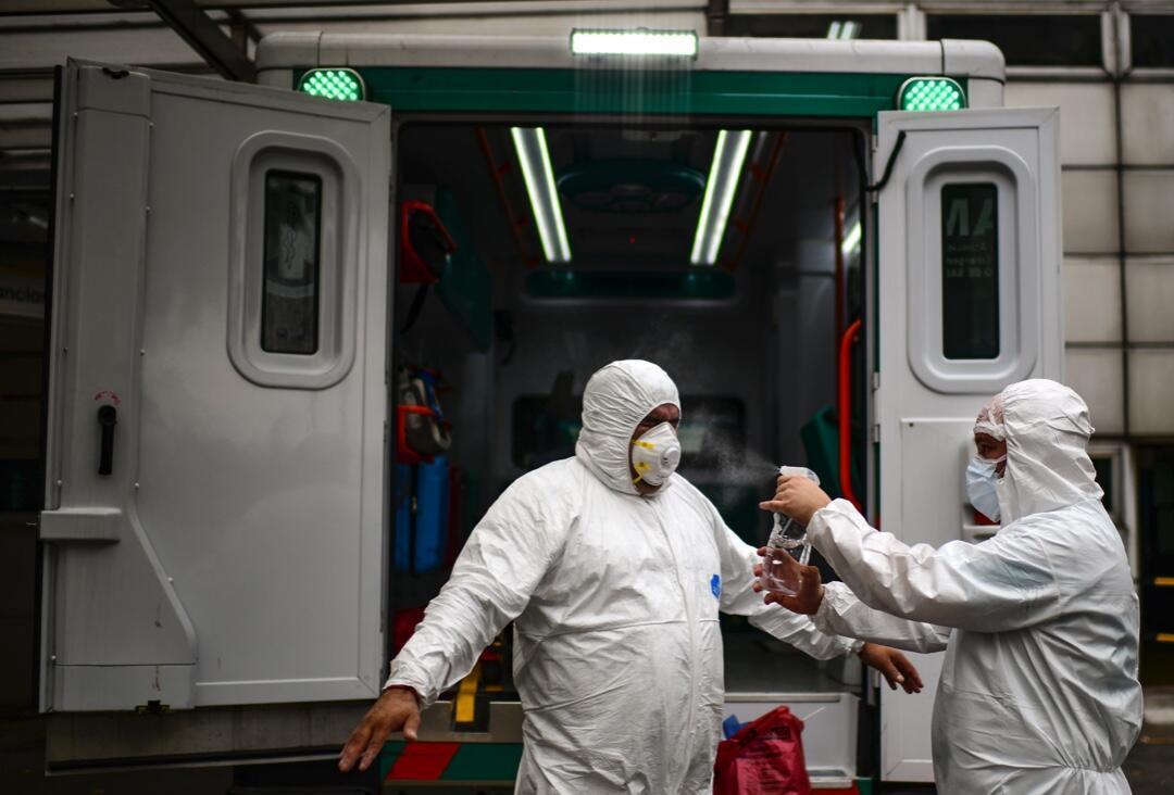 Médicos del Sistema de Emergencia Médica (SAME) de Buenos Aires, Argentina, se rocían alcohol ante un hospital después de trasladar a un paciente con síntomas de Covid-19 el 20 de mayo de 2020.