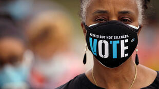 A woman wears a mask with a message urging voter participation while she waits in line to enter a polling place on the first day of the state's in-person early voting for the general election in Durham, North Carolina, US on October 15, 2020.