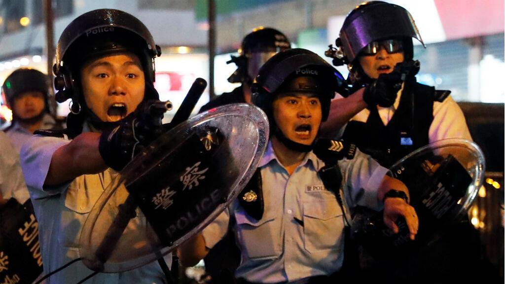 Un agente de policía apunta a los manifestantes con un arma durante las manifestaciones en Hong Kong del pasado 25 de agosto