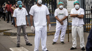 Health workers protest about the lack of protective medical equipment outside the Hipolito Unanue hospital in Lima