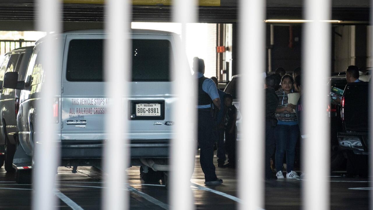 Migrantes salen de camionetas de la gurdia fronteriza para dirigirse al Edificio Federal Richard C. White en el centro de El Paso el 12 de junio.