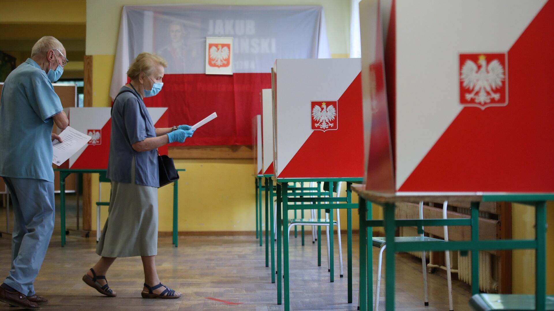 بولنديان يرتديان قناعين طبيين للوقاية من فيروس كورونا يدليان بصوتيهما في الدورة الأولى من الانتخابات الرئاسية، 28 يونيو/حزيران 2020.