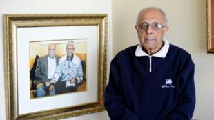 Ahmed Kathrada pose en juillet 2012, alors qu'il a 82 ans, devant une photo de lui et Nelson Mandela.