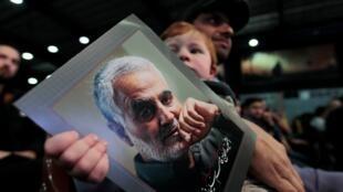 Un partidario del líder de Hezbolá del Líbano, Sayyed Hassan Nasrallah, lleva a un niño con una foto del último comandante de la Fuerza Quds de Irán, Qassem Soleimani, durante una manifestación que conmemora a los líderes asesinados de Hezbolá en los suburbios del sur de Beirut, Líbano, 16 de febrero de 2020.