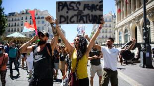 """Un manifestante sostiene una pancarta que reza """"Pase forzado = dictadura"""" durante una manifestación en Marsella, el 17 de julio de 2021, contra las nuevas restricciones sanitarias en Francia."""