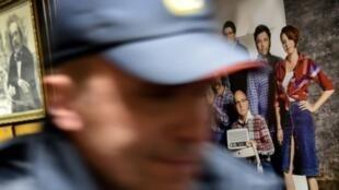 """ضابط شرطة يمر أمام صورة تظهر فيها الصحافية ومقدمة البرامج في إذاعة """"صدى موسكو""""، تاتيانا فلغنغوير التي تعرضت للطعن في العنق صباح 23 تشرين الأول/أكتوبر 2017 بمقر الإذاعة بموسكو."""