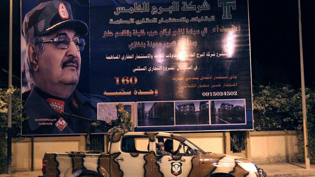 Des membres des forces spéciales libyennes loyales au maréchal Haftar (en photo sur le panneau) patrouillent dans les rues de Benghazi, le 19 septembre 2017.