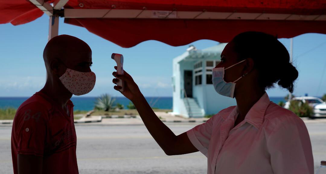 Una doctora revisa la temperatura de un hombre que sale de la provincia de La Habana en medio de un alza de los casos de coronavirus en la capital cubana. Boca de Jaruco, Cuba, el 10 de agosto de 2020.
