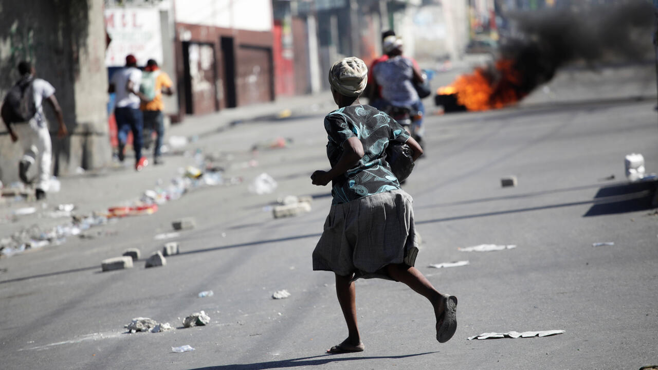Una mujer corre durante los enfrentamientos en una manifestación organizada por la oposición para exigir la renuncia del presidente Jovenel Moïse, en las calles de Puerto Príncipe, Haití, 27 de octubre de 2019.
