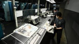 Staff work at the printing facility of Apple Daily in Hong Kong