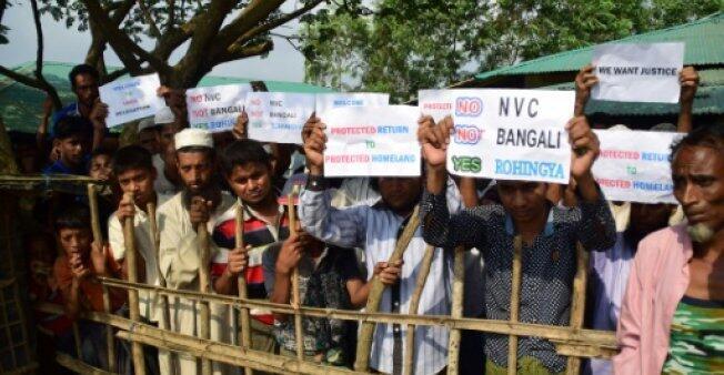 لاجئون روهينغا يحملون لافتات على مرأى من أعضاء فريق مجلس الأمن الدولي