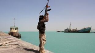 صورة التقطت في الثامن من شباط/فبراير 2017 يظهر فيها عنصر من القوات الموالية للحكومة اليمنية حاملا سلاحه في مرفأ مدينة المخا على البحر الأحمر