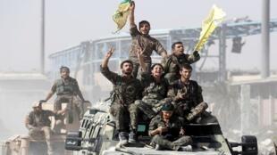 مقاتلو قوات سوريا الديمقراطية يركبون السيارات العسكرية أثناء احتفالهم بالنصر في الرقة، سوريا، 17 أكتوبر/تشرين الأول 2017