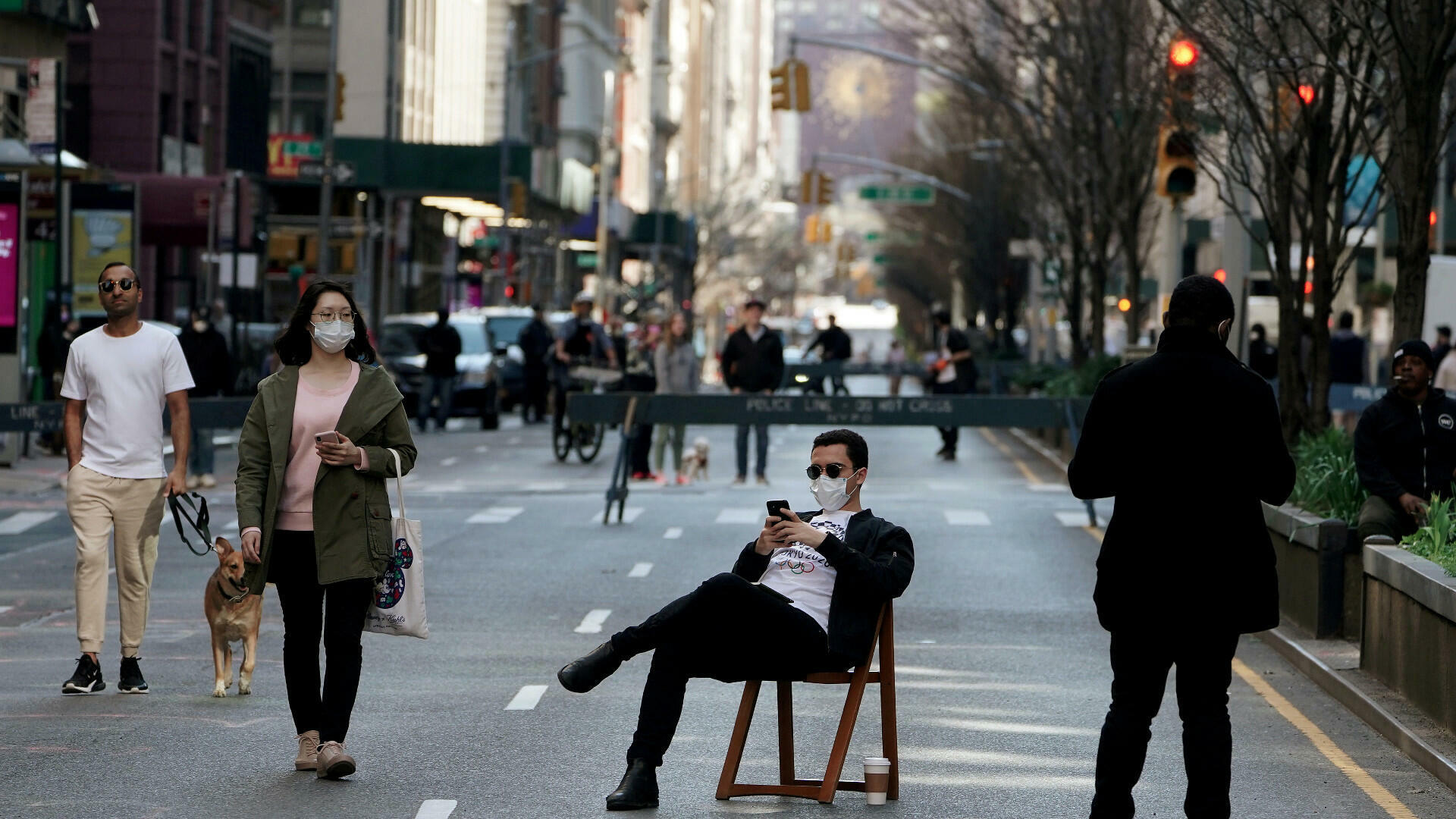 Un hombre se sienta en una silla mientras la gente camina en Park Avenue que estaba cerrada al tráfico de vehículos durante el brote de la enfermedad por coronavirus (COVID-19), en el distrito de Manhattan de la ciudad de Nueva York