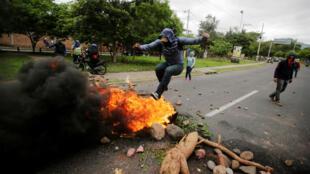 Un manifestante salta sobre una barricada durante una protesta contra el presidente del gobierno de Honduras, Juan Orlando Hernández, en Tegucigalpa, Honduras, 20 de junio de 2019.