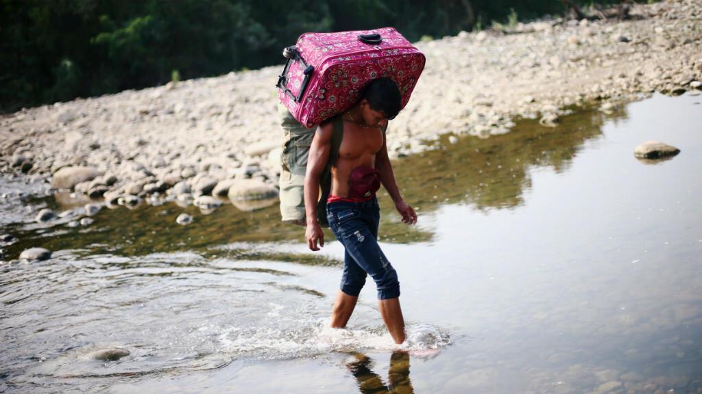 Un hombre con una maleta al hombro cruza el río Táchira a las afueras de Cúcuta, en la frontera entre Colombia y Venezuela, el 26 de febrero de 2019.