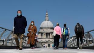 People wearing face masks cross Millennium Bridge, as the spread of the coronavirus disease (COVID-19) continues, in London, Britain, April 25, 2020.
