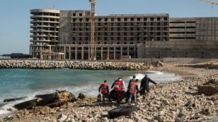 Des membres du Croissant-Rouge libyen transportent les corps des migrants morts noyés au large des côtes libyennes, le 4 janvier 2017.