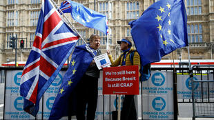Anti-Brexit protesters hold flags outside the Houses of Parliament in London on October 15, 2019.