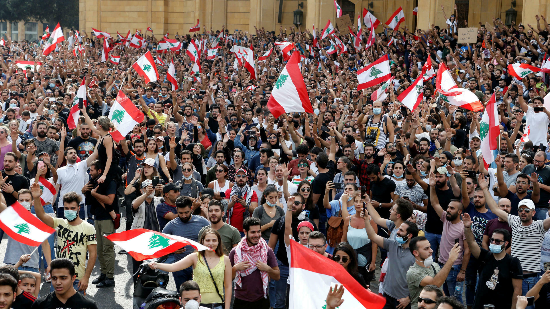 Los manifestantes sostienen banderas libanesas mientras se reúnen durante una protesta por el deterioro de la situación económica, en Beirut, Líbano, el 18 de octubre de 2019.
