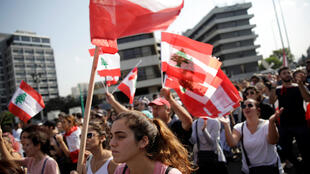 المتظاهرون يحملون الأعلام الوطنية خلال الاحتجاجات المستمرة المناهضة للحكومة في بيروت ، لبنان 6 نوفمبر 2019