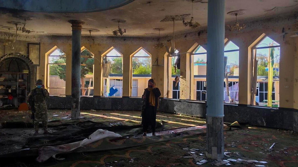 Militares y civiles revisan la mezquita donde se detonó una explosión que mató a al menos 100 personas en Kunduz, Afganistán, el 8 de octubre de 2021.