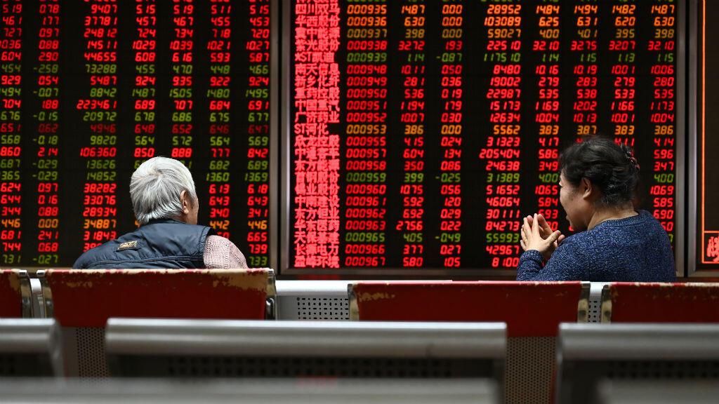 Dos mujeres frente a una tabla de precios de acciones, en Beijing el 21 de enero de 2019. La economía de China creció a su ritmo más lento en casi tres décadas en 2018.