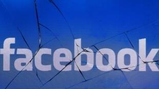 شعار شبكة التواصل الاجتماعي فيس بوك على شاشة مكسورة لهاتف محمول، 16 مايو/أيار 2016