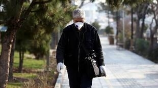 A man wearing a face mask walks down a street in the Iranian capital Tehran.